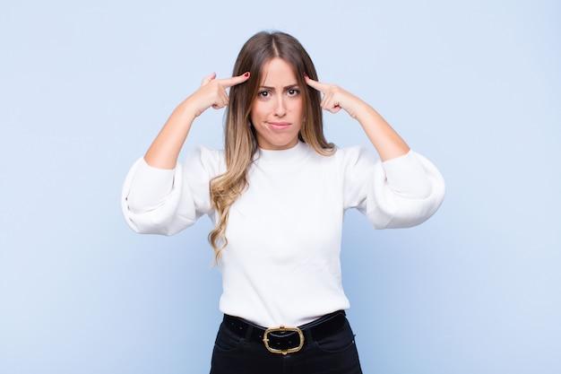 Jeune jolie femme hispanique avec un regard sérieux et concentré, un brainstorming et une réflexion sur un problème difficile contre le mur bleu