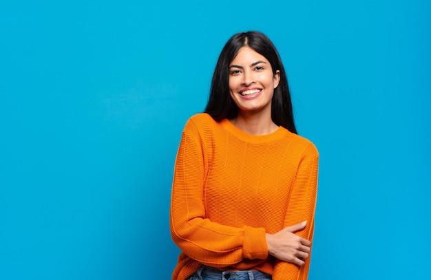 Jeune jolie femme hispanique riant timidement et joyeusement, avec une attitude amicale et positive mais peu sûre