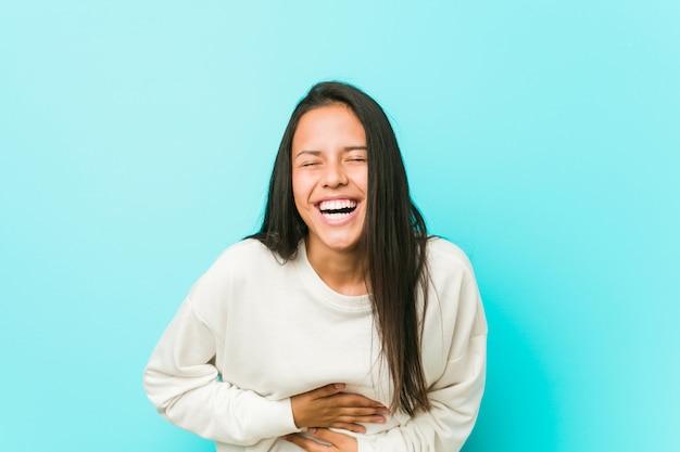 Jeune jolie femme hispanique rit joyeusement et s'amuse en gardant les mains sur le ventre.