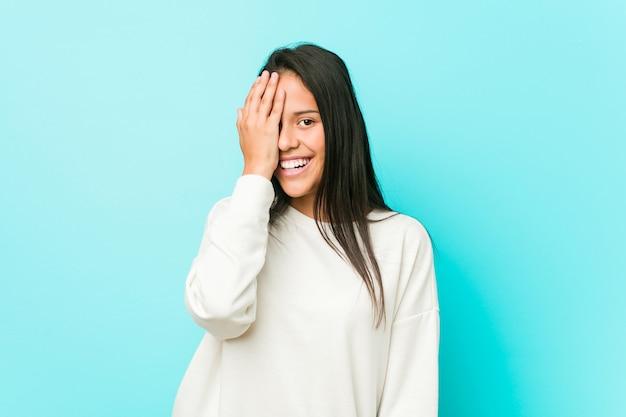 Jeune jolie femme hispanique s'amuser couvrant la moitié du visage avec palme.