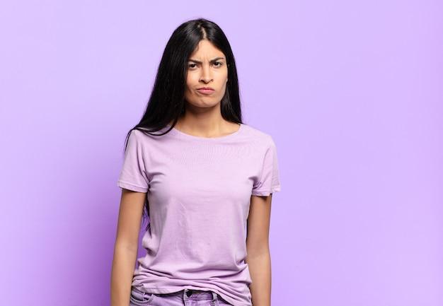 Jeune jolie femme hispanique se sentant confuse et douteuse, se demandant ou essayant de choisir ou de prendre une décision