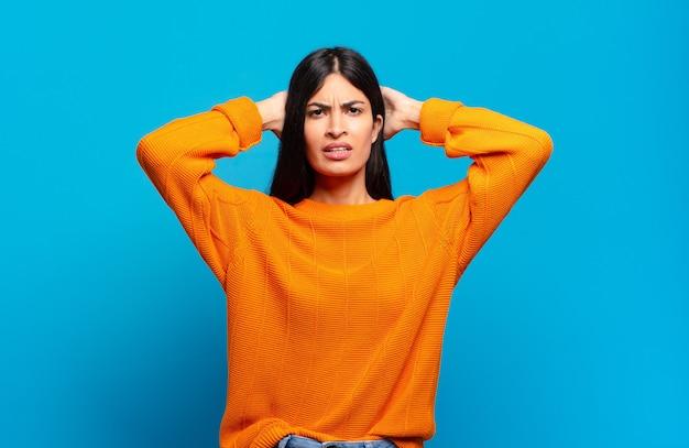 Jeune jolie femme hispanique se sentant stressée, inquiète, anxieuse ou effrayée, les mains sur la tête, paniquée par erreur