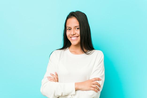 Jeune jolie femme hispanique souriante confiante avec les bras croisés.