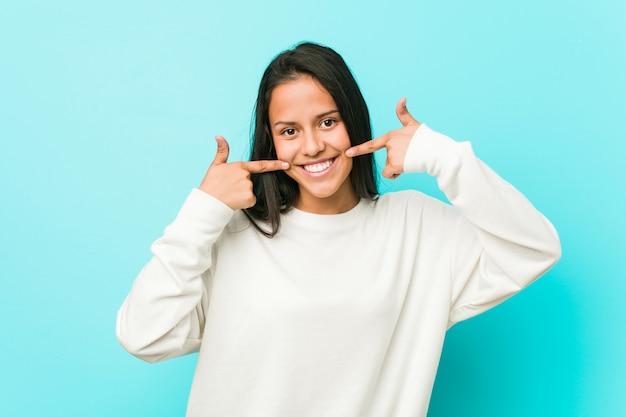 Jeune jolie femme hispanique sourit, pointant les doigts sur la bouche.