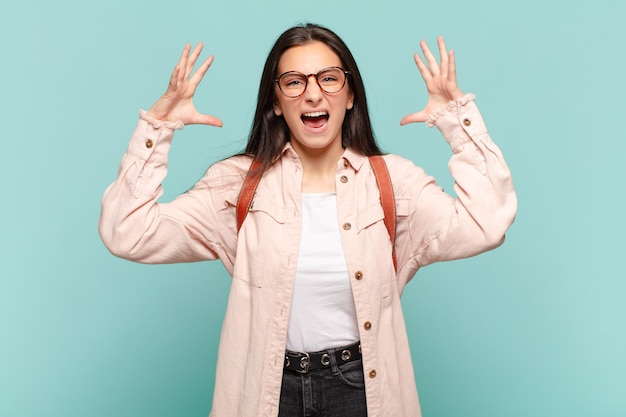Jeune jolie femme hurlant les mains en l'air, se sentant furieuse, frustrée, stressée et bouleversée. concept étudiant