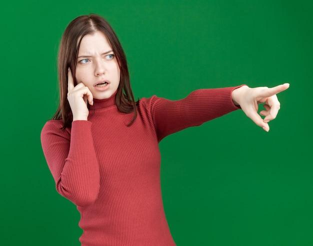Jeune jolie femme impressionnée faisant un geste de réflexion regardant et pointant sur le côté