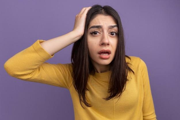 Jeune jolie femme impressionnée regardant l'avant en mettant la main sur la tête isolée sur un mur violet