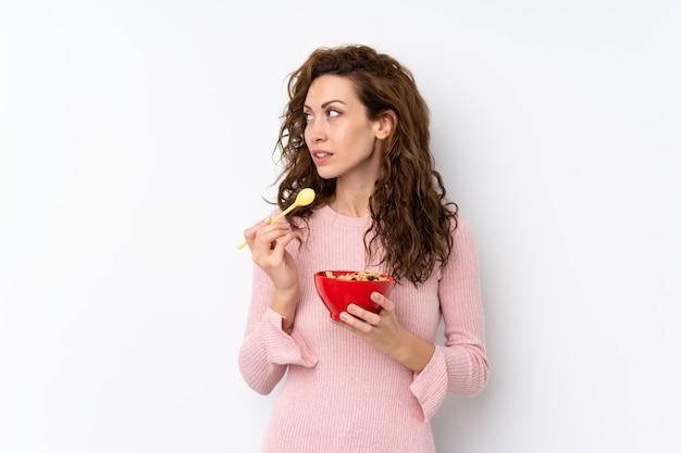 Jeune jolie femme sur isolé tenant un bol de céréales et de penser