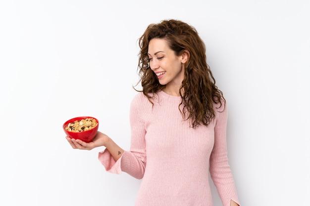 Jeune jolie femme sur isolé tenant un bol de céréales