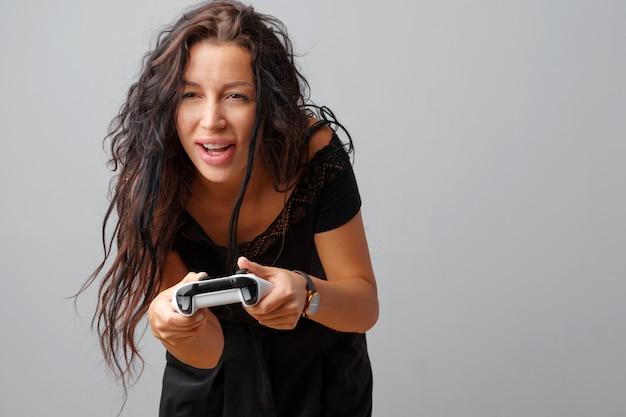 Jeune jolie femme jouant avec une manette de jeu sur un fond gris