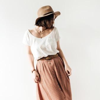 Jeune jolie femme en jupe longue, chapeau, chemisier blanc sur blanc