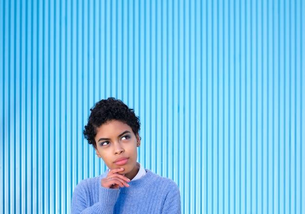 Jeune, jolie femme latina portant un pull décontracté sur un mur bleu, pensant inquiète à une question, inquiète et nerveuse avec sa main sur son menton.