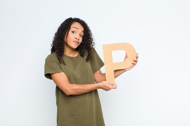 Jeune jolie femme latine confuse, douteuse, réfléchie, tenant la lettre p de l'alphabet pour former un mot ou une phrase.
