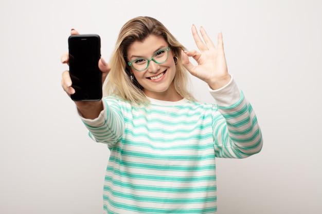Jeune jolie femme latine contre un mur plat avec un téléphone intelligent