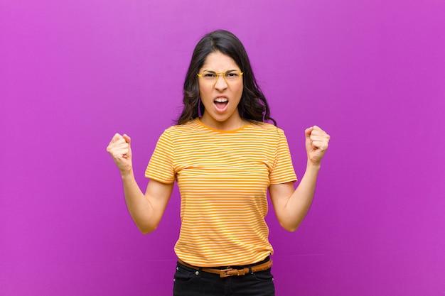 Jeune jolie femme latine criant agressivement avec une expression de colère ou avec les poings serrés célébrant le succès contre le mur violet