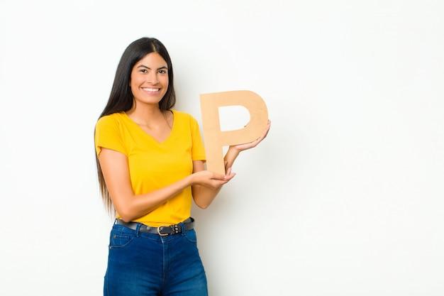 Jeune jolie femme latine excitée, heureuse, joyeuse, tenant la lettre p de l'alphabet pour former un mot ou une phrase.