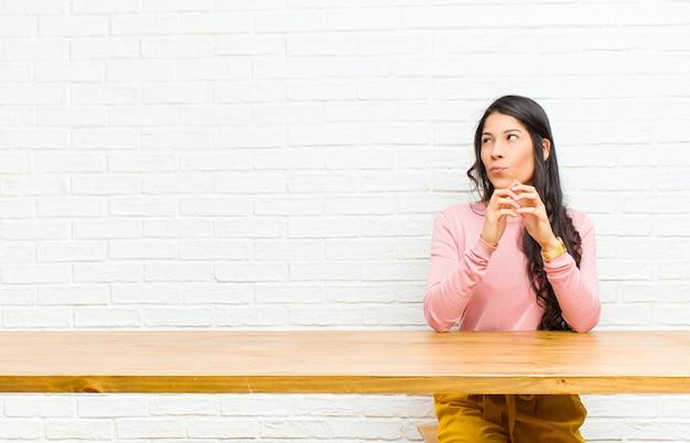 Jeune jolie femme latine intriguant et conspirant, pensant astuces et astuces sournoises, rusé et trahissant assis devant une table