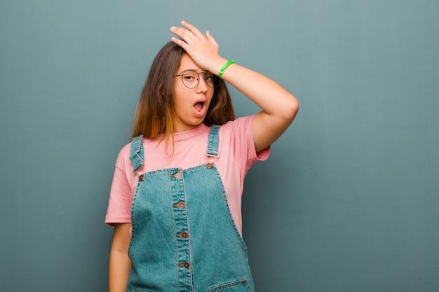 Jeune jolie femme latine levant la paume au front pensant oops, après avoir fait une erreur stupide ou se souvenir, se sentir stupide contre le mur de grunge