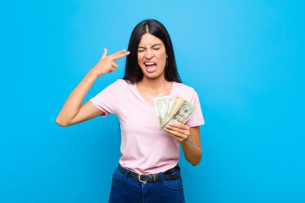 Jeune jolie femme latine à la malheureuse et stressée, geste de suicide faisant signe de pistolet avec la main, pointant la tête sur le mur