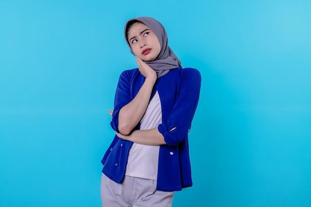 Jeune jolie femme latine qui a l'air concentrée et réfléchit sérieusement à une idée, imaginant une solution à un défi ou à un problème contre le mur bleu