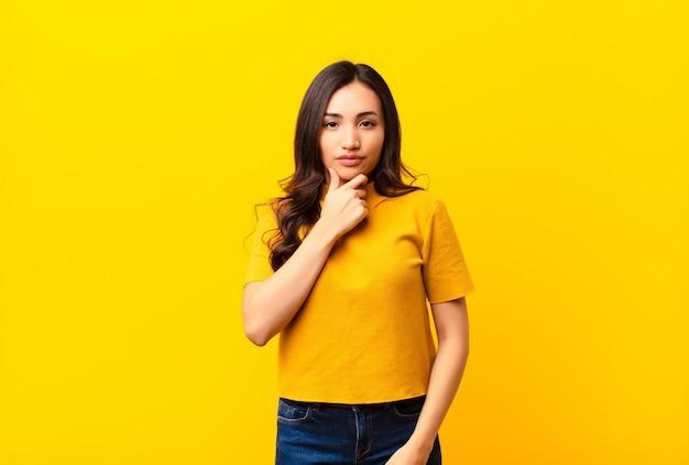 Jeune jolie femme latine à la recherche de sérieux, confus, incertain et réfléchi, doutant parmi les options ou les choix sur le mur