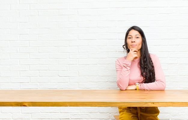 Jeune jolie femme latine à la recherche de sérieux, confuse, incertaine et réfléchie, doutant des options ou des choix assis devant une table
