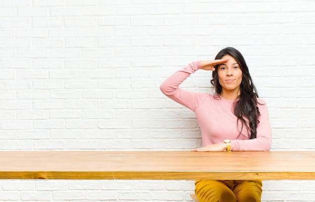 Jeune jolie femme latine saluant la caméra avec un salut militaire dans un acte d'honneur et de patriotisme, montrant le respect assise devant une table