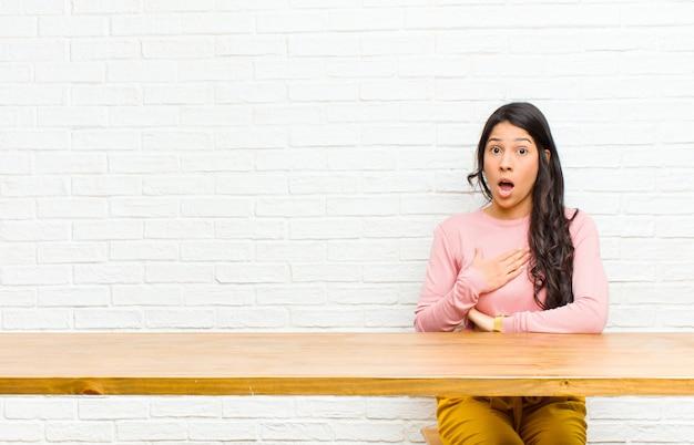 Jeune jolie femme latine se sentant choquée, étonnée et surprise, avec la main sur la poitrine et la bouche ouverte, en disant qui, moi? assis devant une table