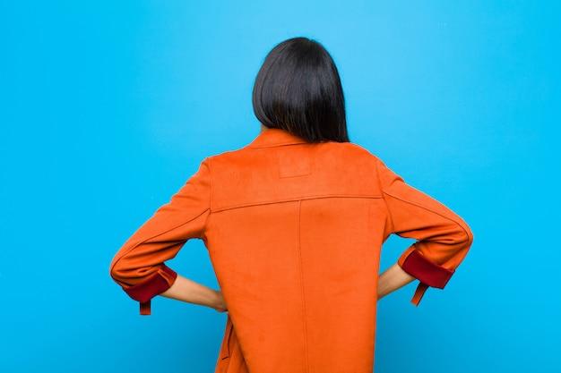 Jeune jolie femme latine se sentant confus ou plein ou des doutes et des questions, se demandant, avec les mains sur les hanches, vue arrière sur le mur