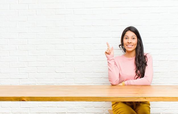 Jeune jolie femme latine souriante gaie et joyeuse, pointant vers le haut avec une main pour copier l'espace assis devant une table