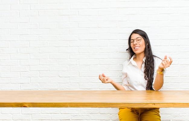 Jeune jolie femme latine souriante, insouciante, détendue et heureuse, dansant et écoutant de la musique, s'amusant lors d'une soirée assise devant une table