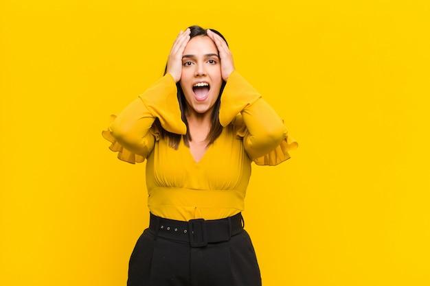 Jeune jolie femme levant les mains à la tête, bouche bée, se sentant extrêmement chanceuse, surprise, excitée et heureuse sur le mur orange