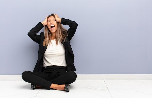 Jeune jolie femme levant les mains à la tête, bouche bée, se sentant extrêmement chanceux, surpris, excité et heureux concept d'entreprise