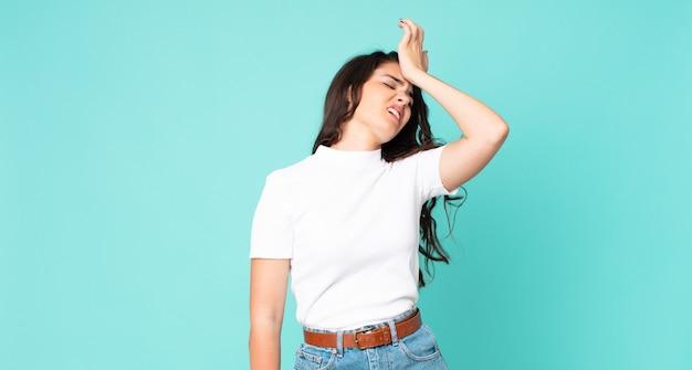 Jeune jolie femme levant la paume vers le front pensant oops, après avoir fait une erreur stupide ou s'être souvenue, se sentir stupide
