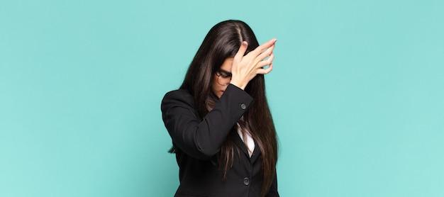 Jeune jolie femme levant la paume vers le front en pensant oups, après avoir fait une erreur stupide ou s'être souvenue, se sentant stupide. concept d'entreprise