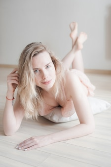Jeune jolie femme en lingerie douce, allongée sur le sol. beauté visage féminin sans maquillage