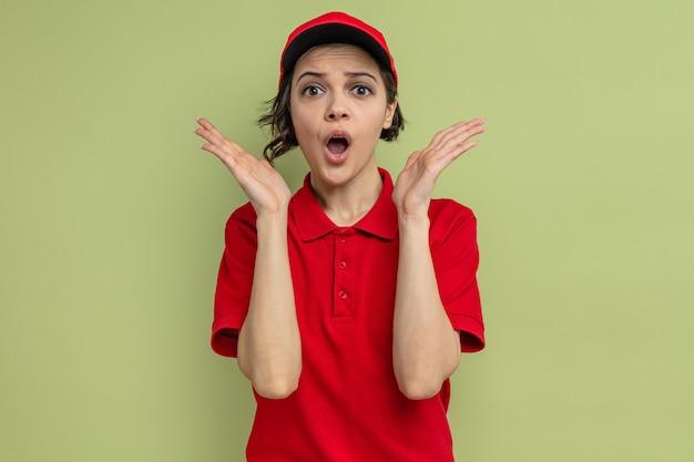 Jeune jolie femme de livraison anxieuse debout avec les mains levées