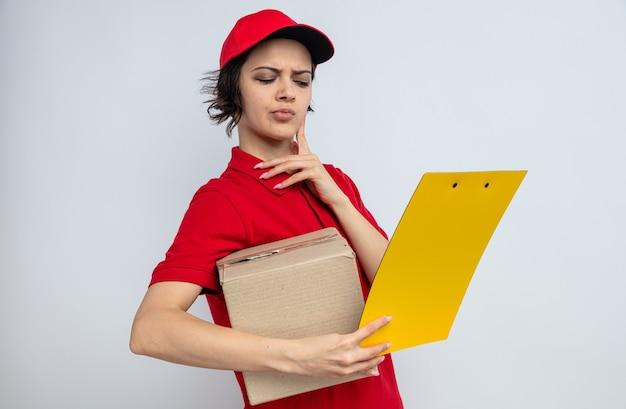 Jeune jolie femme de livraison réfléchie tenant une boîte en carton et regardant le presse-papiers