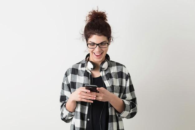 Jeune jolie femme à lunettes, à l'aide de smartphone, expression du visage surpris, émotion drôle, rire, positif, heureux, casque, isolé, chemise à carreaux, style hipster, étudiant, message de saisie