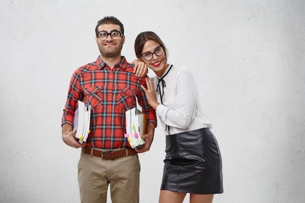 Jeune jolie femme à lunettes à la mode, porte un chemisier blanc et une jupe noire s'appuie sur l'épaule de son petit ami