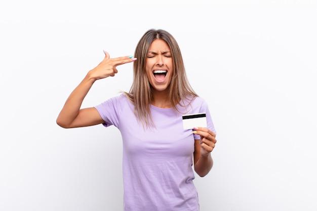 Jeune jolie femme à la malheureuse et stressée, geste de suicide faisant signe de pistolet avec la main, montrant la tête avec une carte de crédit