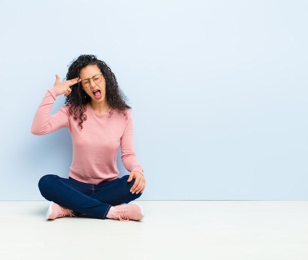 Jeune jolie femme à la malheureuse et stressée, geste de suicide faisant signe de pistolet avec la main, pointant la tête assise sur le sol