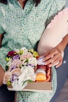 Jeune jolie femme mangeant un gâteau dans une cuisine moderne. vêtements pour la maison.