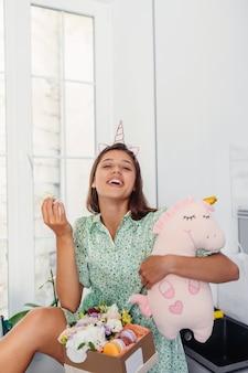 Jeune jolie femme mangeant un gâteau dans une cuisine moderne.