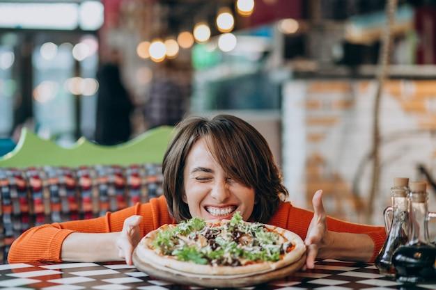 Jeune jolie femme mangeant une pizza au bar à pizza