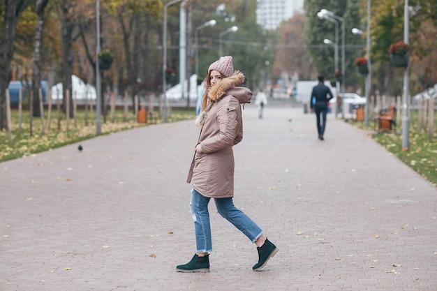 Jeune jolie femme marchant dans le parc en automne.
