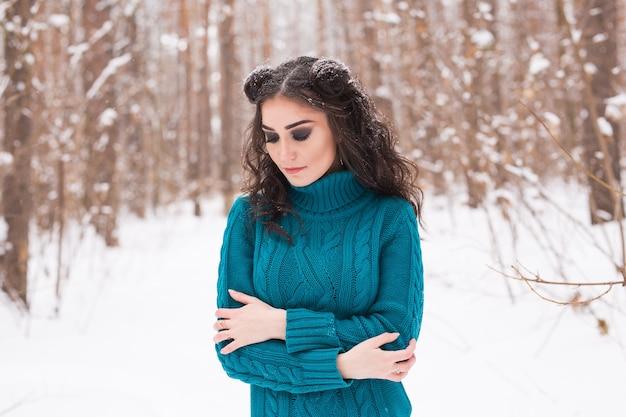 Jeune jolie femme marchant dans le parc enneigé d'hiver à la journée ensoleillée