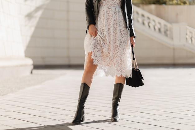 Jeune jolie femme marchant dans la rue en tenue à la mode, tenant sac à main, vêtue d'une veste en cuir noir et robe en dentelle blanche, style printemps automne, temps chaud et ensoleillé, look romantique