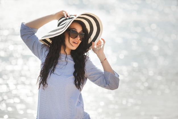 Jeune jolie femme marchant sur une plage. jolie fille adulte près de l'eau relaxante. belle femme sur la mer