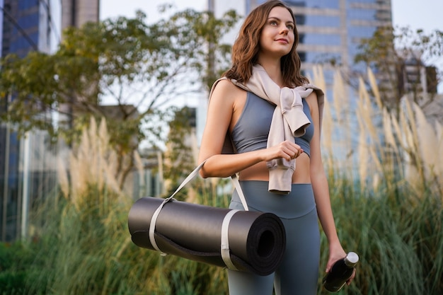Jeune jolie femme marchant seule au parc de la ville après son cours de yoga fitness
